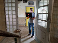 Man standing in abandoned house holding a high-tech laptop